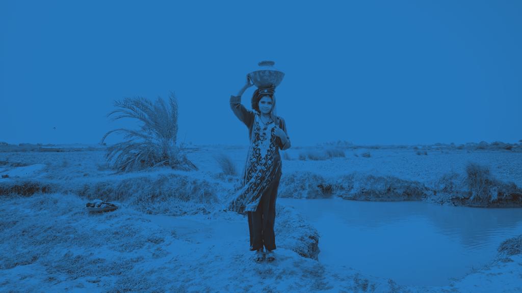 Flicka som bär en kruka på huvudet, vid en flod